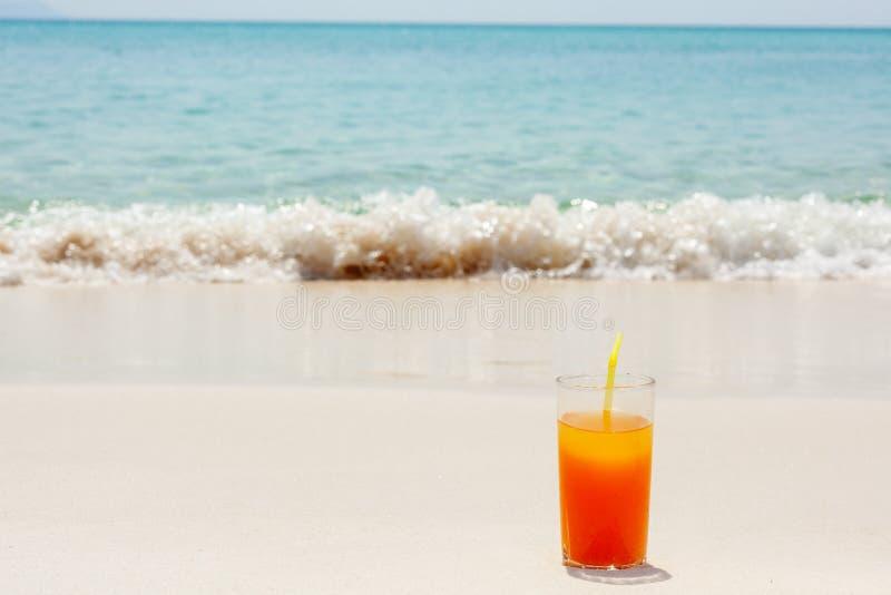 Tasse en verre avec le jus d'orange avec une paille sur la plage sur le sable blanc contre une mer bleue photo stock
