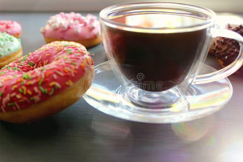Tasse en verre de café chaud sur une table noire entourée par les butées toriques colorées image libre de droits