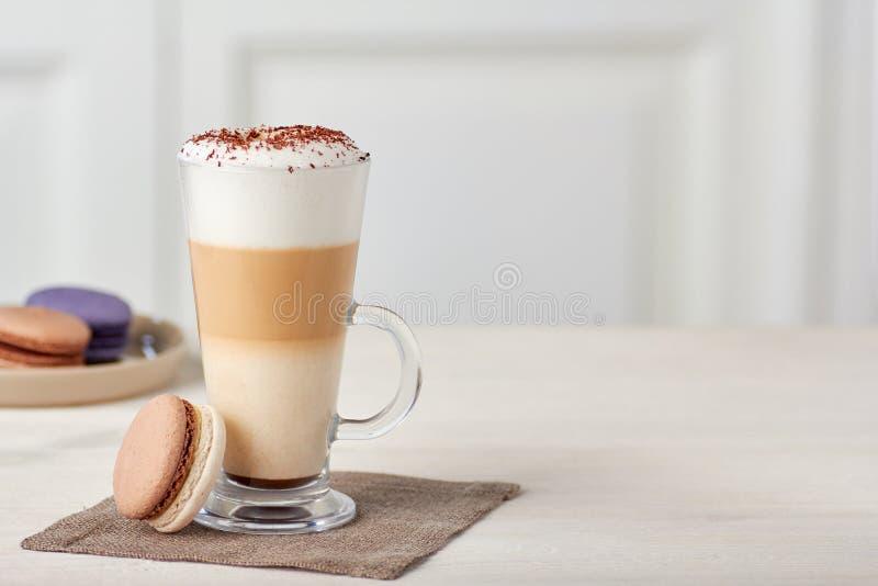 Tasse en verre de latte de café et de macarons colorés sur la table en bois image libre de droits