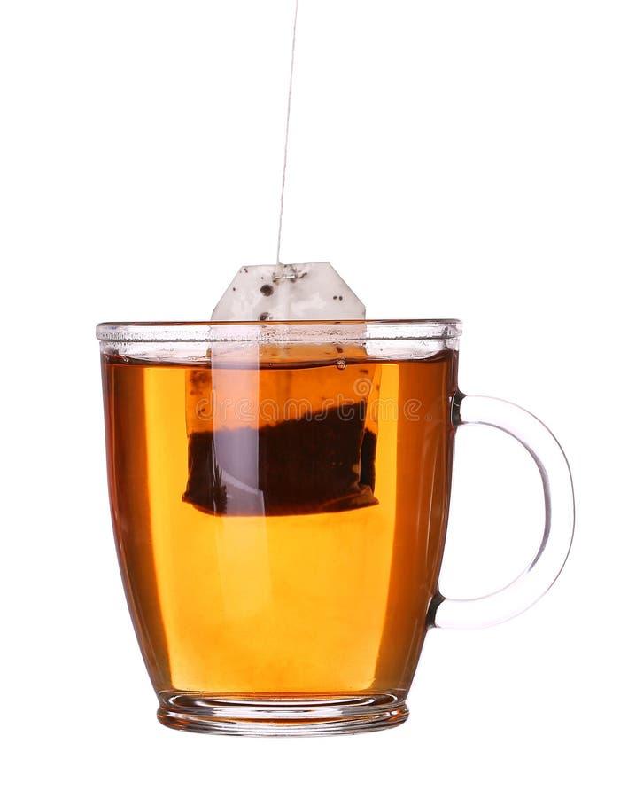 Tasse en verre de thé avec le sachet à thé d'isolement sur le blanc photographie stock libre de droits