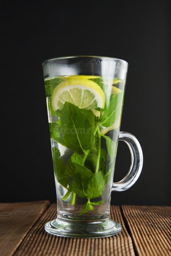 Tasse en verre de tranches en bon état de citron d'ith de thé et de fleurs jaunes sur le fond Table en bois et fond noir photo stock