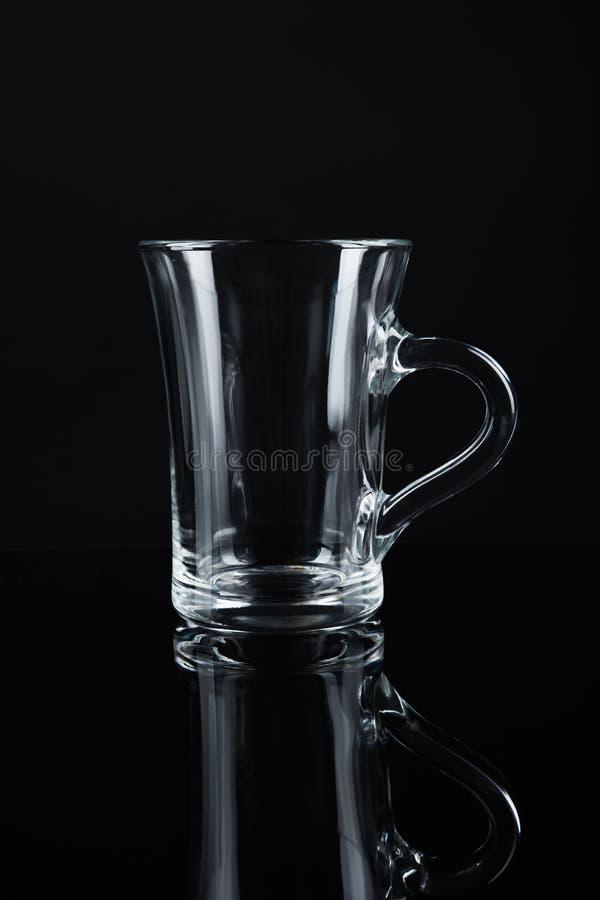 Tasse en verre vide propre sur le noir photographie stock libre de droits