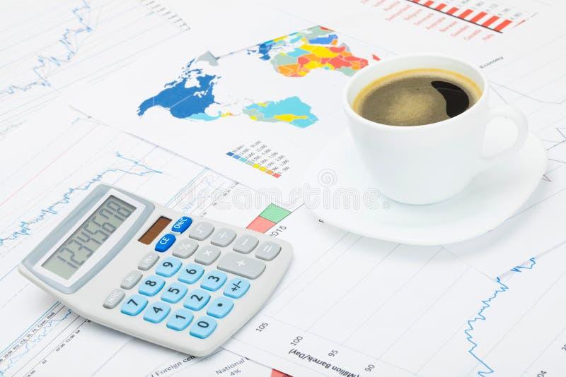 Tasse et calculatrice de café au-dessus des diagrammes financiers photographie stock