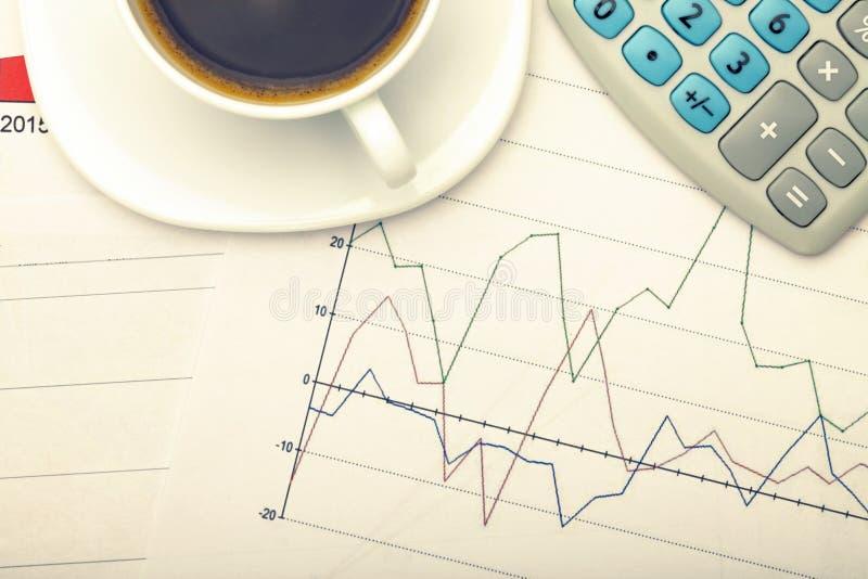 Tasse et calculatrice de café au-dessus des diagrammes financiers Image filtrée : effet de vintage traité par croix photos stock