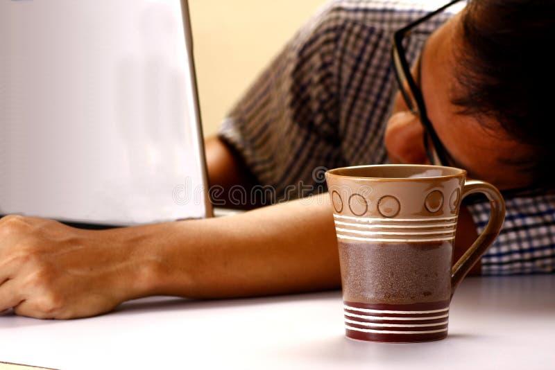 Tasse et homme de café dormant devant un ordinateur portable à l'arrière-plan photographie stock libre de droits