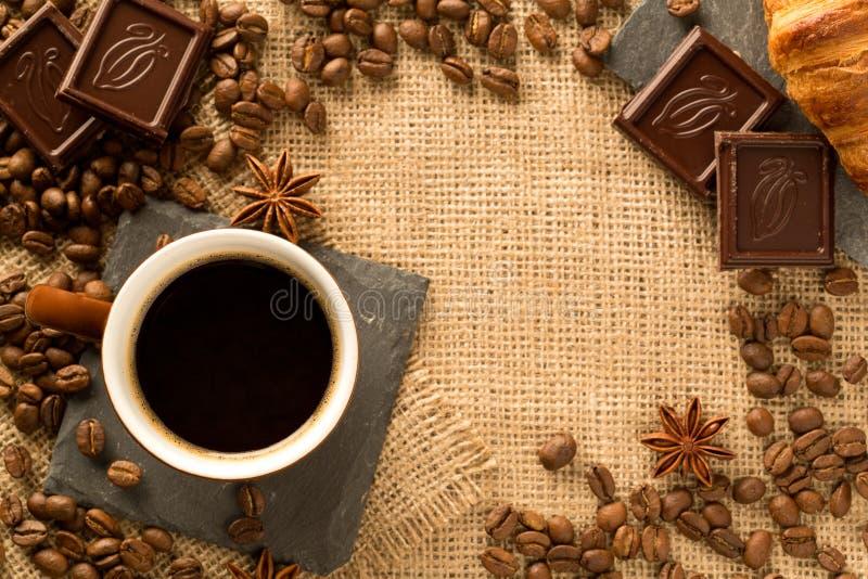 Tasse et ingrédients de café sur le fond de toile de jute images stock