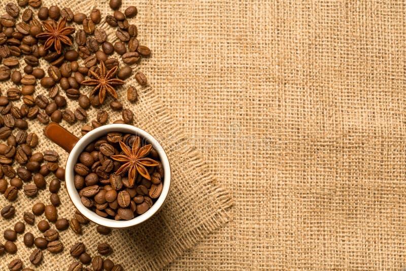 Tasse et ingrédients de café sur le fond de toile de jute image stock