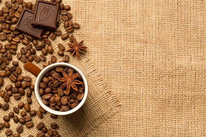 Tasse et ingrédients de café sur le fond de toile de jute photos stock