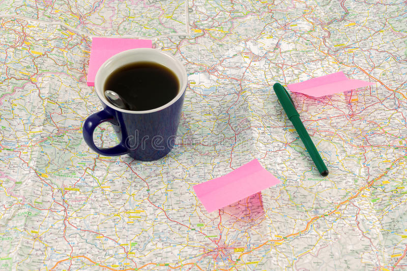 Tasse et papier de café bleus avec la pointe sur la carte, préparation pour le voyage image stock