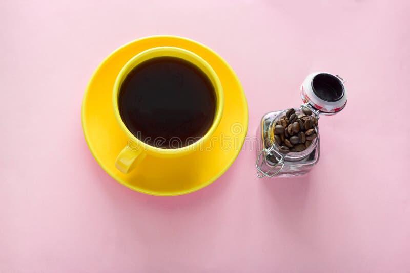 tasse et pot de café jaunes avec des grains de café sur un fond rose photos libres de droits