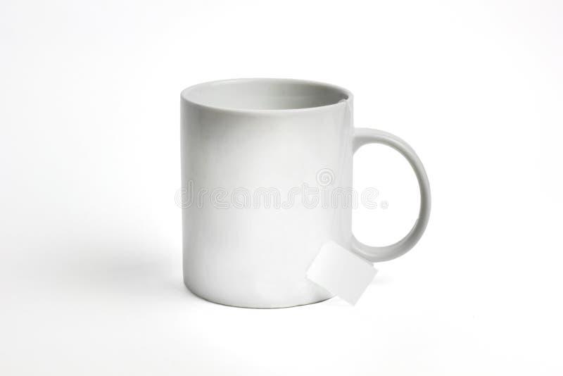 Tasse et sac blancs de thé Sur le fond blanc Maquette pour des conceptions photo libre de droits