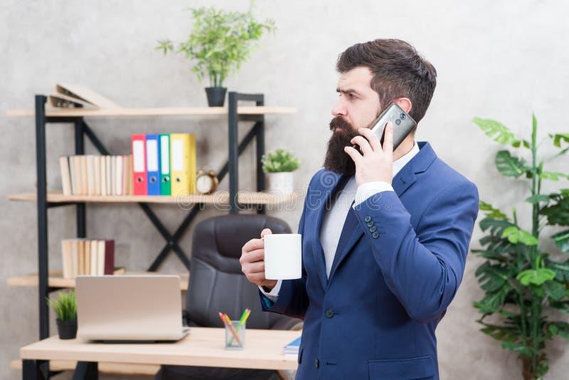 Tasse et smartphone barbus de prise d'homme d'affaires d'homme Appel mobile Jour de début avec du café Coupure de détente de café photographie stock libre de droits