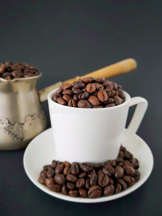 Tasse et soucoupe de café blanc ; grains de café dispersés sur la table À l'arrière-plan est un cezve Fond noir image stock
