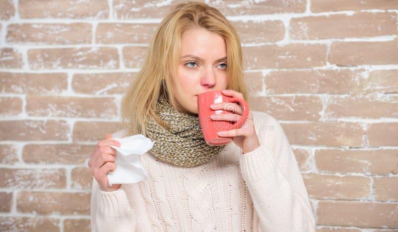 Tasse et tissu de thé de prise de fille Écoulement nasal et d'autres symptômes du froid Remèdes de froid et de grippe Buvez plus  photo stock