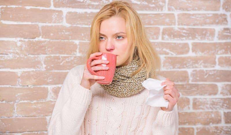 Tasse et tissu de th? de prise de fille ?coulement nasal et d'autres sympt?mes du froid Rem?des de froid et de grippe Buvez plus  photos libres de droits