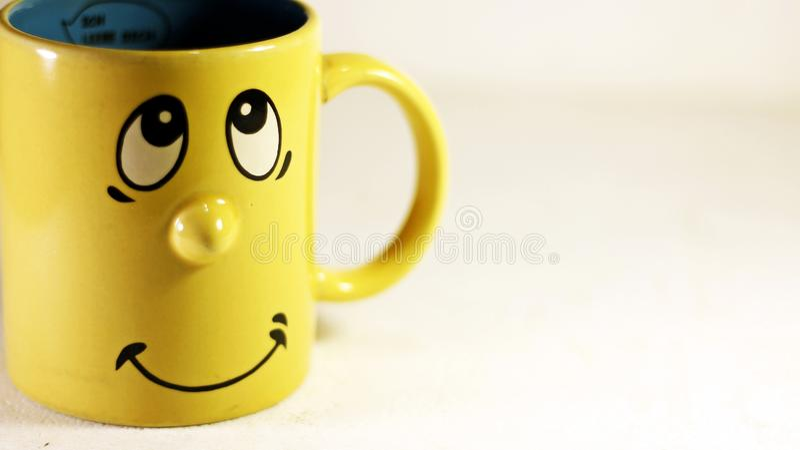 Tasse - gaie et souriante dans la couleur jaune images stock