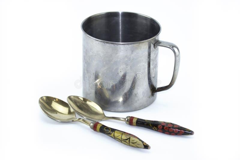 Tasse inoxydable, vieille tasse en m?tal, cuill?res avec les poign?es peintes en bois Vaisselle russe D'isolement sur le fond bla image stock