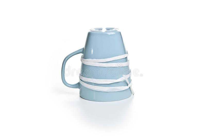 Tasse inversée par bleu attachée avec un ruban image libre de droits