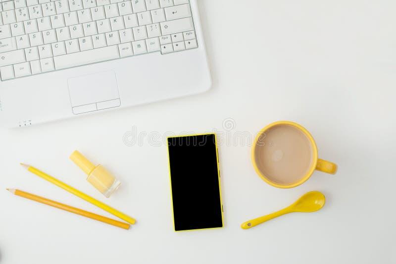 Tasse jaune avec le coffe, téléphone jaune, ordinateur portable et crayons sur le fond blanc Place pour le texte Vue de ci-avant image stock