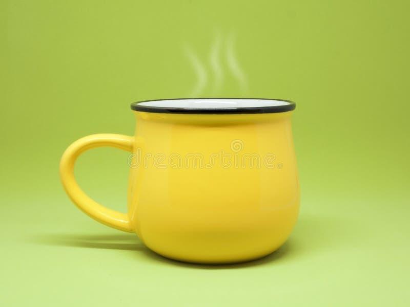 Tasse jaune d'isolement sur un fond vert, vapeur se levant  images libres de droits