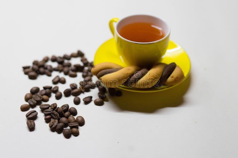 Tasse jaune de thé, de graines de café et de biscuits images libres de droits