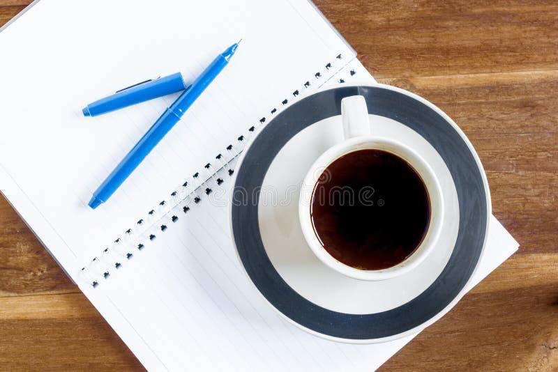 Tasse Kaffee über Notizbuch auf Holztisch stockfoto