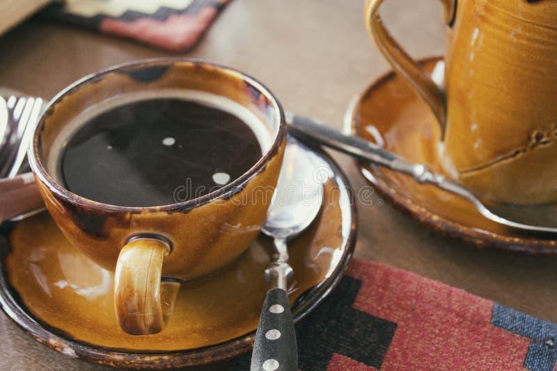 Tasse Kaffee auf altem h?lzernem Schreibtisch Kaffeepause im selektiven Fokus des Morgens in einem caffee stockfotografie