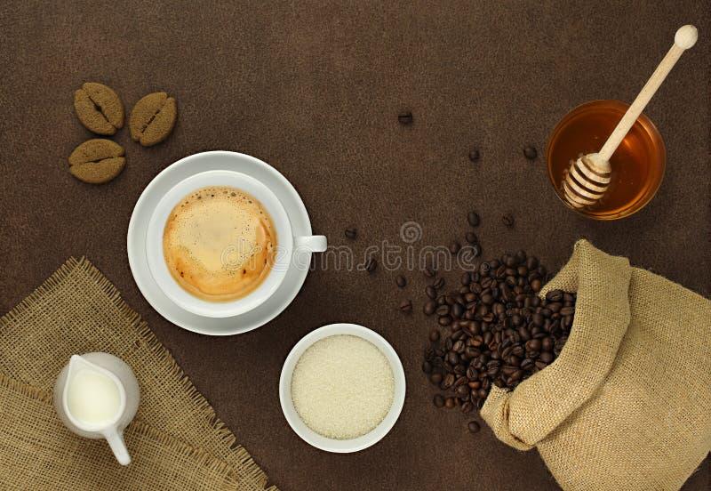 Tasse Kaffee auf dem Tisch mit Bohnen, Zucker und Honig lizenzfreies stockbild