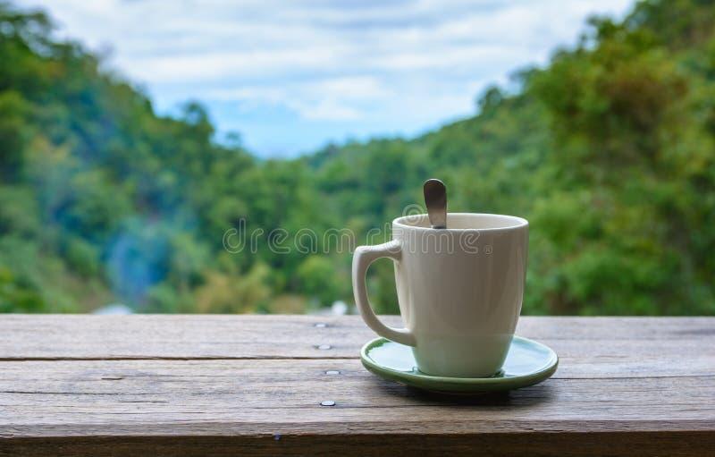 Tasse Kaffee auf hölzernem Balkon lizenzfreie stockfotografie