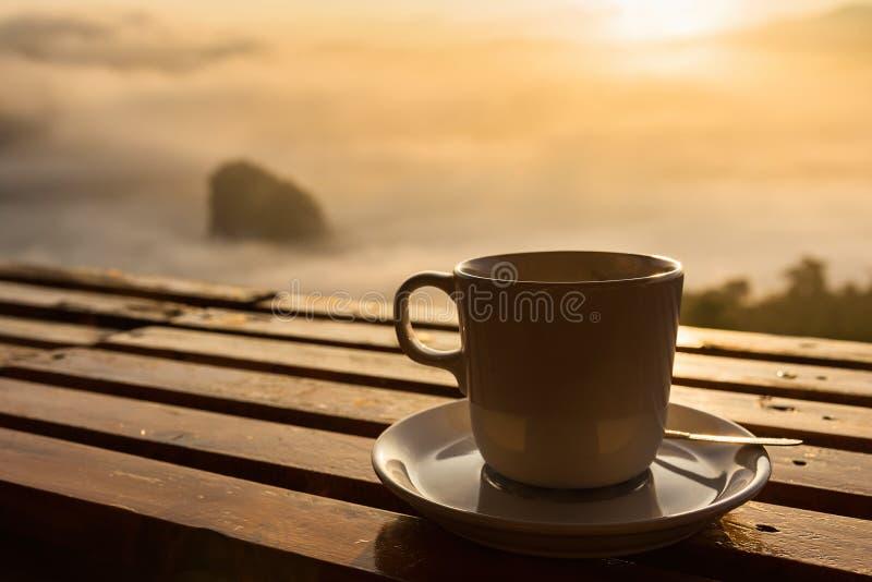 Tasse Kaffee auf Holzfußboden mit nebelhaftem und Gebirgshintergrund T stockfotografie