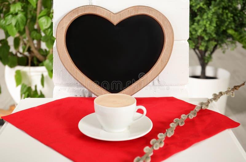 Tasse Kaffee auf Serviette nahe dem Herzen geformt lizenzfreies stockfoto