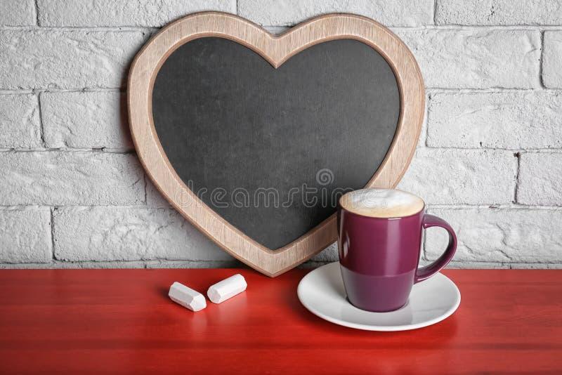 Tasse Kaffee auf Tabelle nahe dem Herzen geformt stockfoto