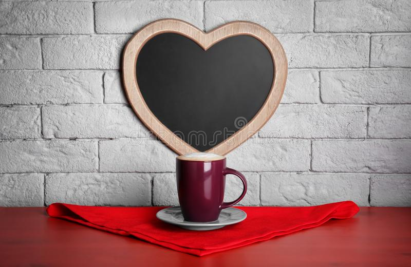 Tasse Kaffee auf Tabelle nahe Herzen lizenzfreie stockfotografie