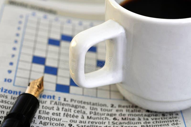 Tasse Kaffee aufgeworfen auf Kreuzworträtsel lizenzfreie stockfotografie