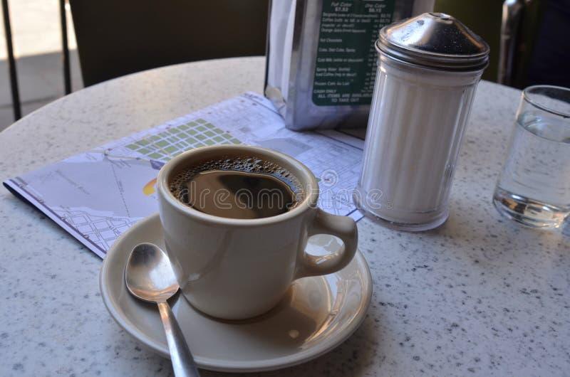 Tasse Kaffee bei Cafe Du Monde in französischem Viertel New Orleans und in der Karte des französischen Viertels lizenzfreie stockfotos