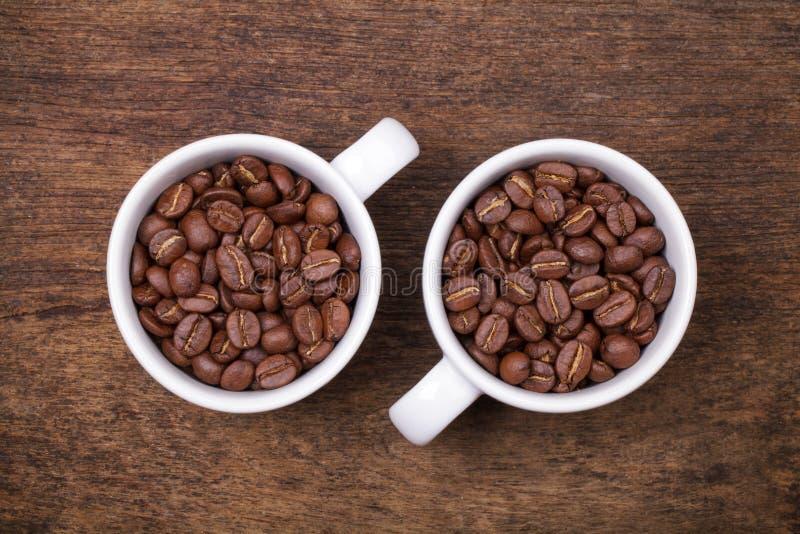 Tasse Kaffee-Bohnen auf dem braunen hölzernen Hintergrund stockbilder
