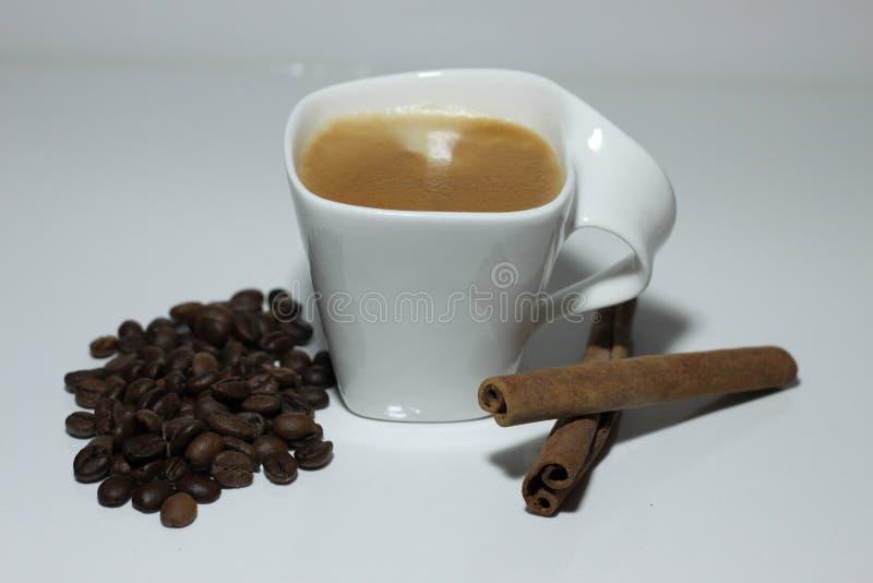 Tasse Kaffee, Bohnen und zwei Zimtstangen stockfotos
