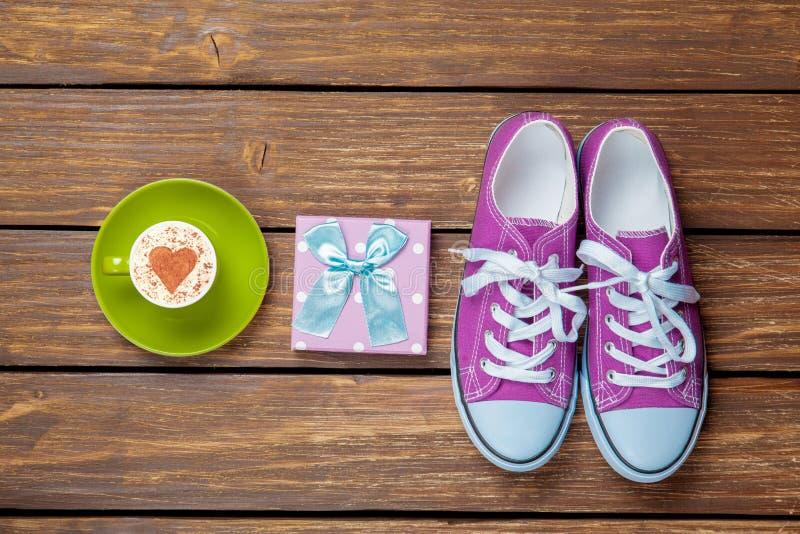 Tasse Kaffee-Cappuccino mit Geschenkbox und Gummiüberschuhen stockfotos