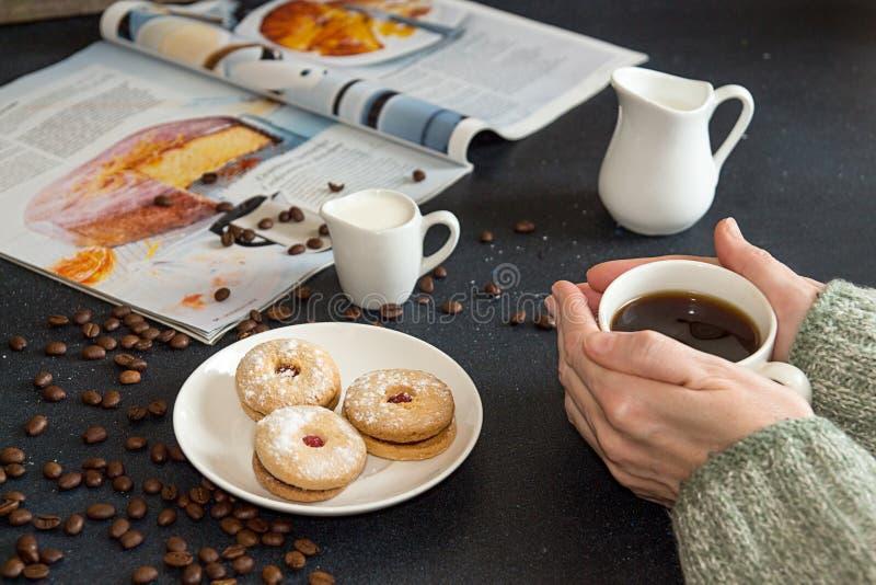 Tasse Kaffee in den Frauenhänden Untertasse mit Plätzchen, gebratenes coffe stockfotografie