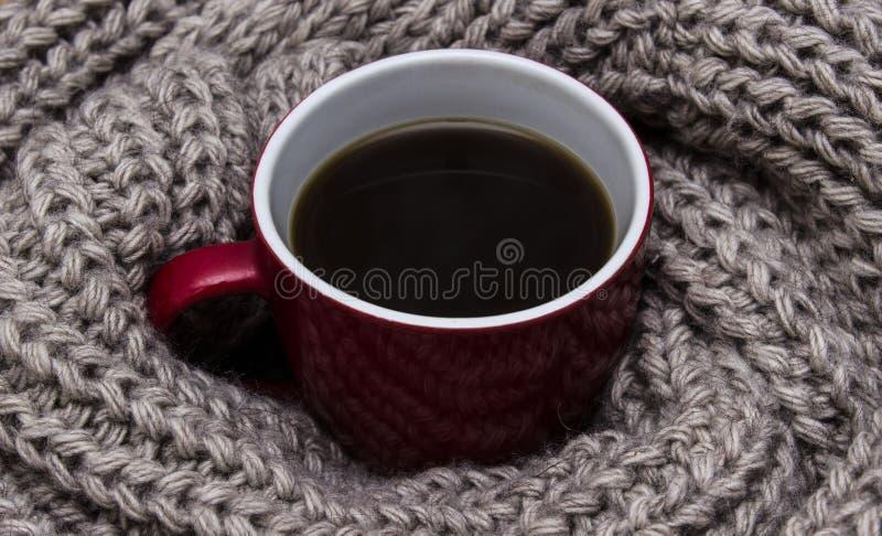Tasse Kaffee eingewickelt im Schal lizenzfreies stockfoto