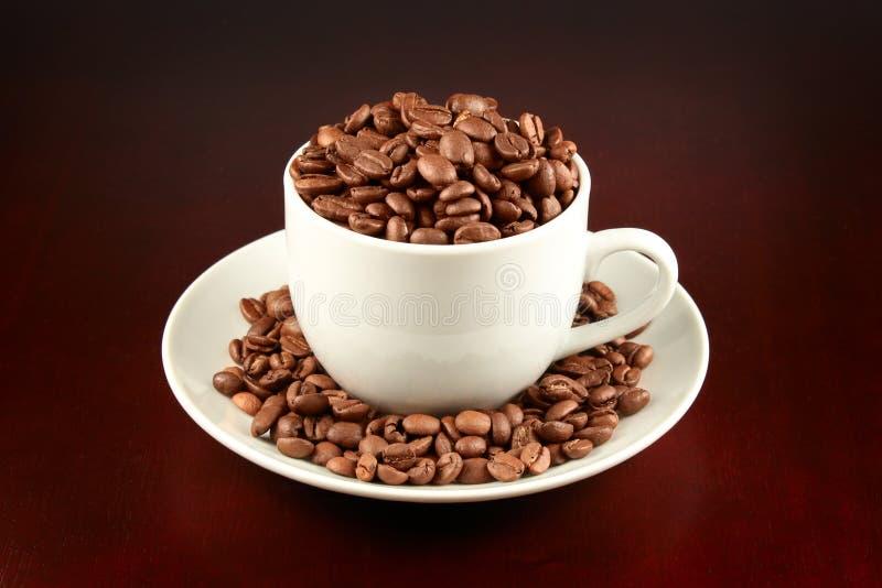 Tasse Kaffee füllte mit Kaffeebohnen auf lizenzfreie stockfotografie