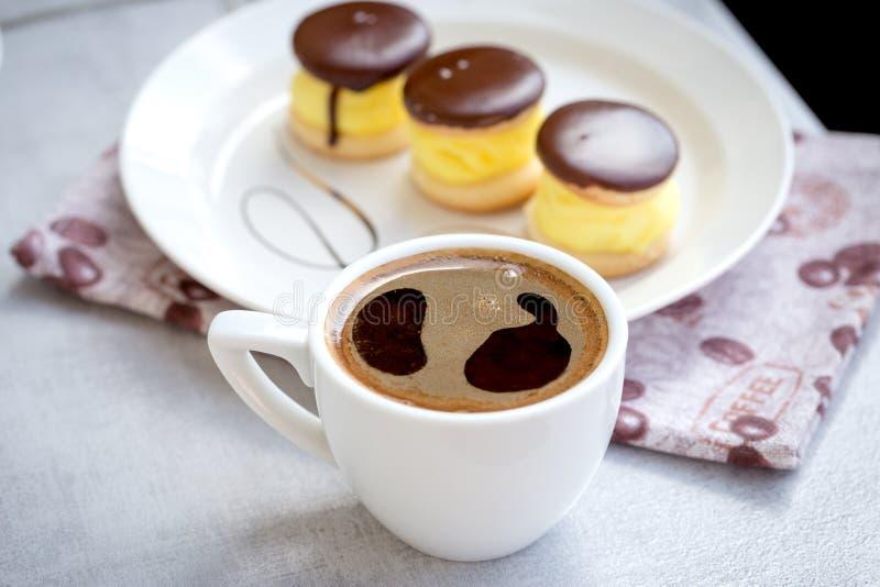 Tasse Kaffee, Kaffeepause und Creme backen für Vergnügen zusammen lizenzfreie stockfotos