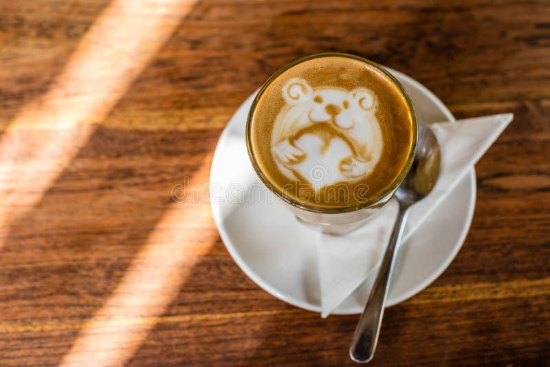 Tasse Kaffee Latte mit Lattekunst eines Bären, der ein Liebesherz, auf dem Holztisch hält lizenzfreies stockfoto