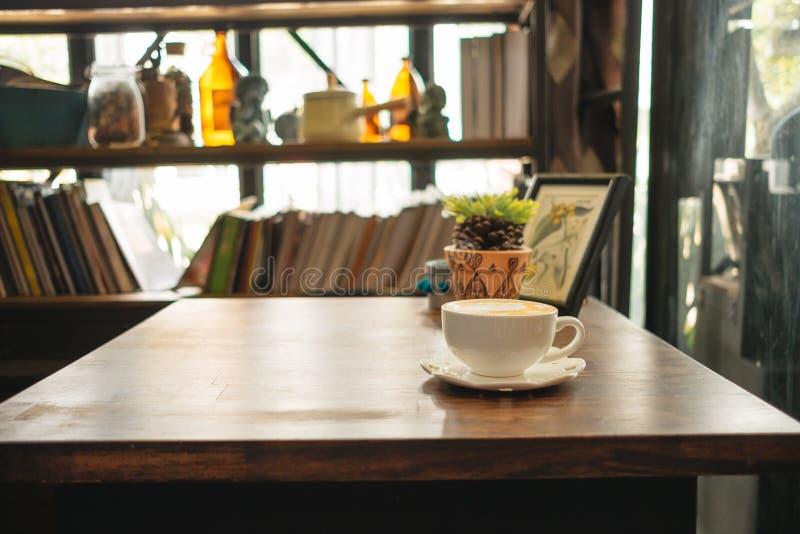 Tasse Kaffee mit Anlagen und Bilderrahmenplatz auf Holz lizenzfreies stockfoto