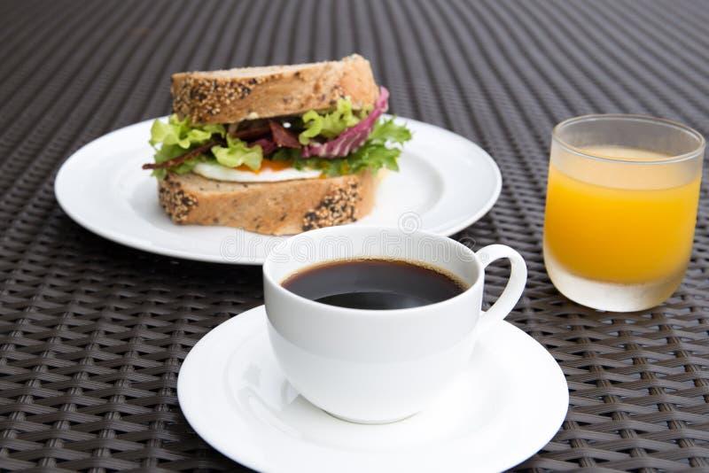 Tasse Kaffee mit egga Sandwich und Orangensaft lizenzfreie stockbilder