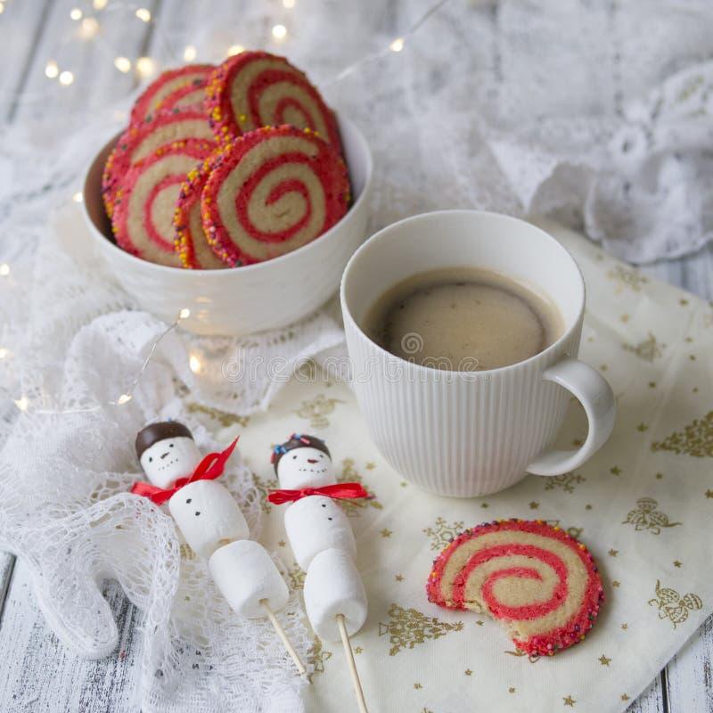 Tasse Kaffee mit einem Eibischschneemann und Plätzchen in Form einer Spirale in der Weihnachtstabelle Gemütliches Winterfrühstück stockfotografie