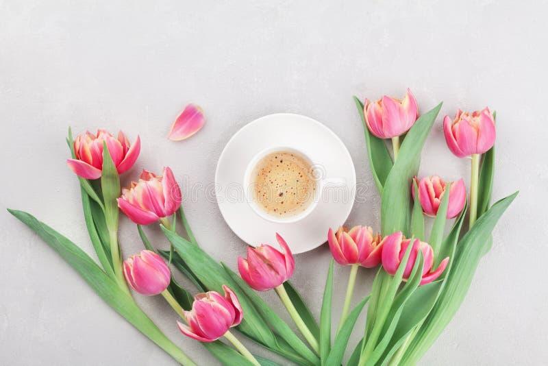 Tasse Kaffee mit Frühlingstulpe blüht für guten Morgen auf grauer Steintischplatteansicht in Ebenenlageart Frühstück auf Müttern  lizenzfreie stockfotografie
