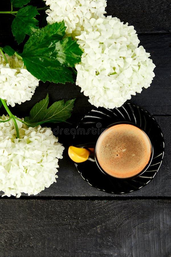 Tasse Kaffee mit gutem Morgen der Blumenstraußhortensie flach stockbild
