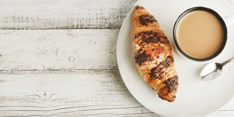 Tasse Kaffee mit Hörnchen auf einer weißen Platte über weißem hölzernem Hintergrund Frühstück, Draufsicht Kopieren Sie Platz fahn lizenzfreie stockfotos