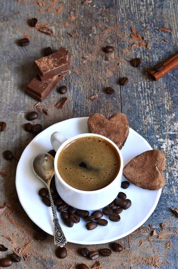 Tasse Kaffee mit Herz-förmigen Schokoladentrüffeln lizenzfreies stockfoto